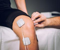 Bein wird mit Elektrotherapie behandelt