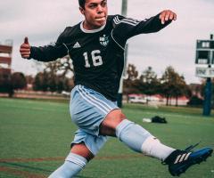 Athletischer Fußballer mit Ball